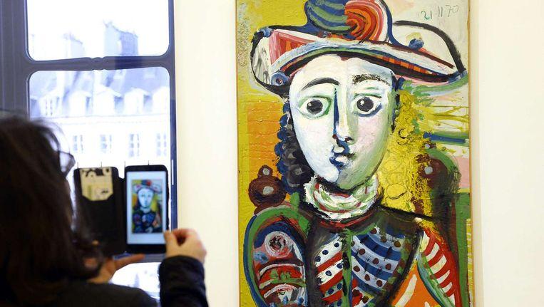Een bezoeker neemt een foto van een echte Picasso tijdens de opening van een tentoonstelling in Parijs. De foto is van oktober. Beeld afp