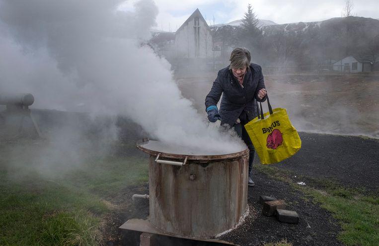 In het IJslandse dorpje Hveragerdi maakt een inwoonster gebruik van een geothermische bron. Brooddeeg verpakt in een leeg melkpak wordt in twaalf uur klaargestoomd tot brood. Beeld Hollandse Hoogte