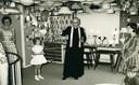 Pastoor Prinsen, pastoor in Udenhout in de jaren 60, zegent de eerste verdieping van de nieuwe winkel van Hoppenbrouwers in. Het familiebedrijf verkocht toen ook lampen. Op de foto van links naar rechts enkele kinderen van Leny en Willy Hoppenbrouwers: Anneke, Maddy in haar communiejurkje, pastoor Prinsen, Agnes en Willy Hoppenbrouwers.