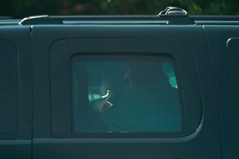 President Donald Trump gebaart naar zijn aanhangers terwijl zijn auto wegrijdt uit de Trump National Golf Club in Sterling, Virginia. Beeld AP