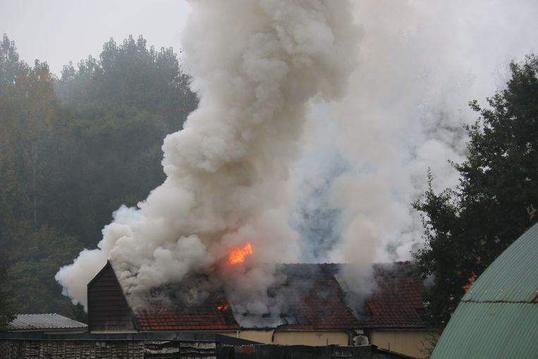 De vlammen slaan door het dak van de woning
