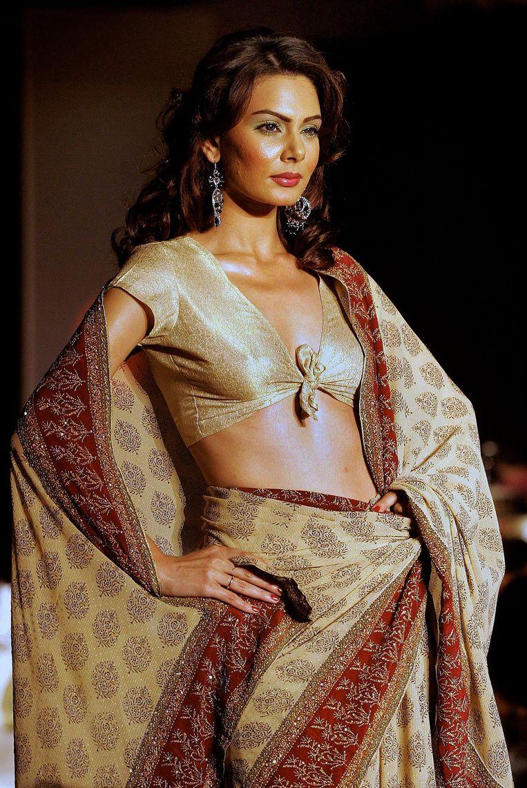 Een Indiaas model tijdens een modeshow in een saree, zoals die nooit op straat gedragen zal worden. Beeld afp