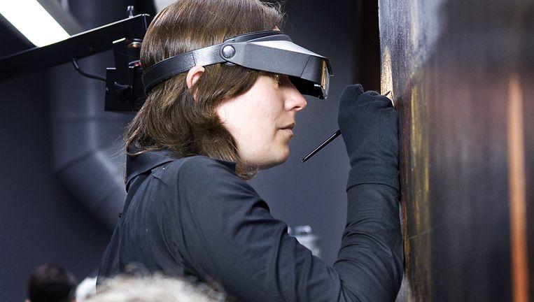Restaurator Susan Smelt aan het werk in het Mauritshuis. Beeld Io Cooman