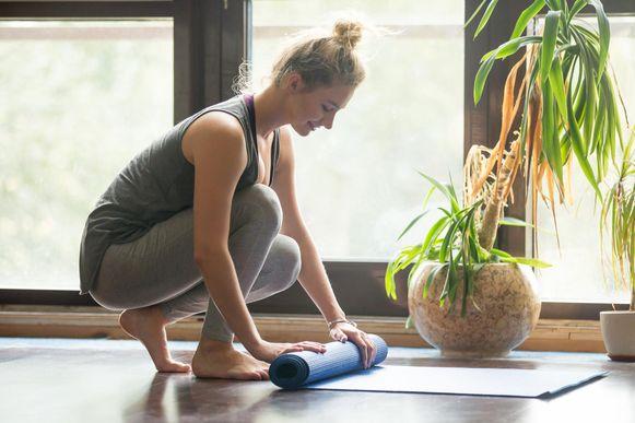 Een vrouw rolt haar yogamatje weer op.
