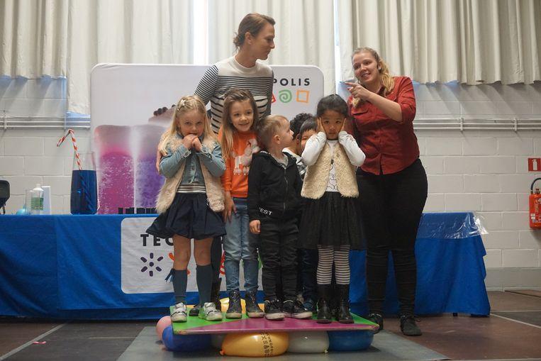 Zes leerlingen én een leerkracht op een plank die op ballonnen ligt. De ballonnen ontploffen niet, al vreest één meisje voor een luide knal.