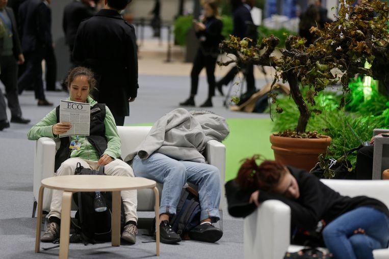 Deelnemers aan de klimaattop in Madrid halen wat slaap in. Beeld AP
