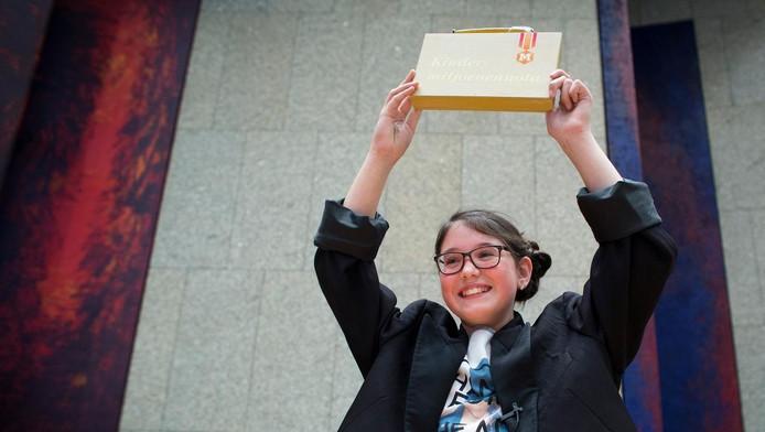 Jade Couwmans van basisschool OBS De Kern uit Ede biedt het koffertje met de Kinder Miljoenennota aan in de Tweede Kamer.