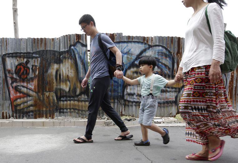 Een gezin in Bangkok loopt langs graffiti van een bedelaar. Beeld EPA