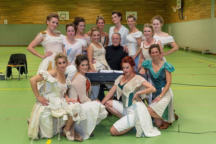 Vertrekkend muzikaal leider Ludo Heesters te midden van een aantal vrouwelijke castleden in de gymzaal van het Goese Lyceum, waar wordt gerepeteerd.