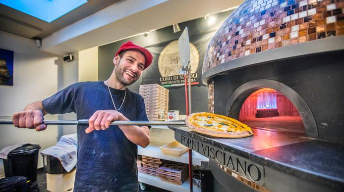 Eigenaar en pizzabakker Francesco Spinuso haalt een versgebakken pompoenpizza uit de forni visciano. Dit is een speciaal uit Italië geïmporteerde pizzaoven.