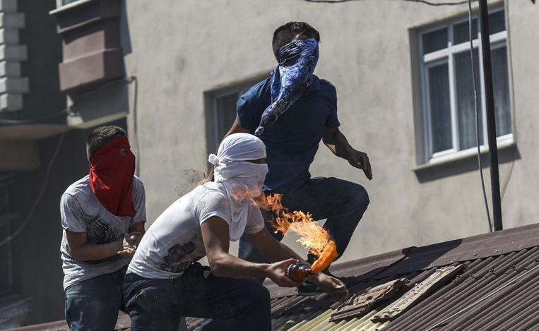 Linkse militanten gooien een molotovcocktail naar de politie tijdens een demonstratie in Istanbul. Beeld afp