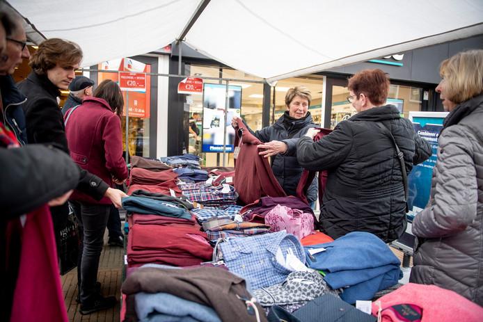 De zussen Roelien Berkhof (met rode trui in de hand) uit Vriezenveen en Marianne Vreker (zwarte jas)  uit Vroomshoop speurden donderdag naar koopjes in het centrum van Rijssen.