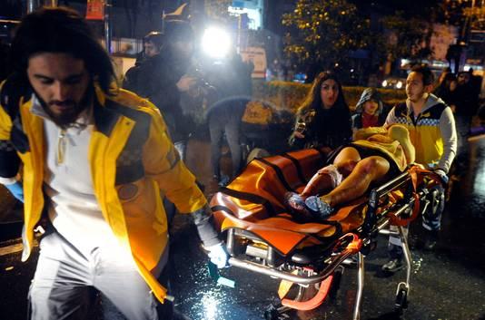 Een slachtoffer wordt door ambulancemedewerkers afgevoerd.