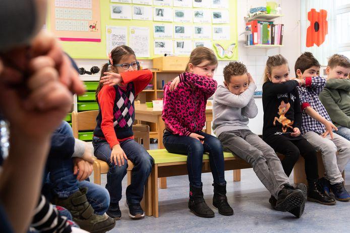 Kinderen in een schoolklas in Breda leren hoe ze beter in hun arm kunnen hoesten dan in hun handen, vanwege mogelijke verspreiding van het virus.