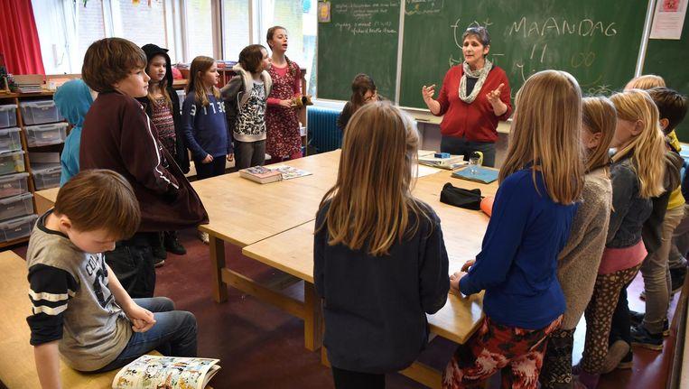 Een leerkracht sluit met haar groep de week af, foto ter illustratie. Beeld Marcel van den Bergh / de Volkskrant