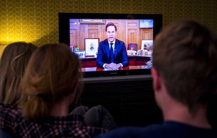 Een gezin kijkt naar de toespraak van Rutte gisteravond.