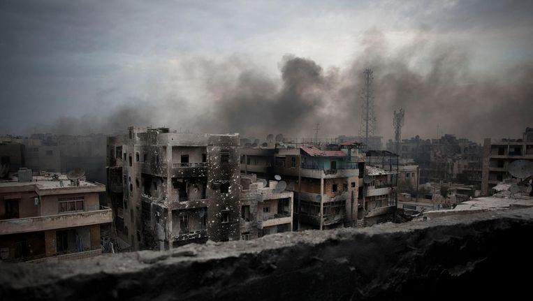 Rook boven een verwoest Aleppo Beeld ap