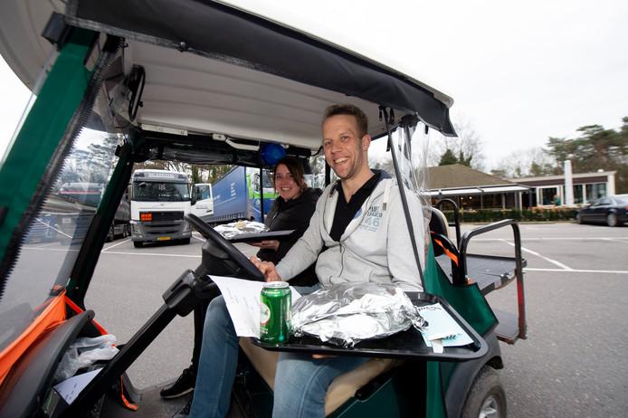 Wegrestaurant Mendel schiet truckers te hulp: nu de deuren dicht moeten blijven brengen ze het eten per golfkar naar de vrachtwagens. Op de foto Dave Buitenhuis en Claudia Hilbrink.