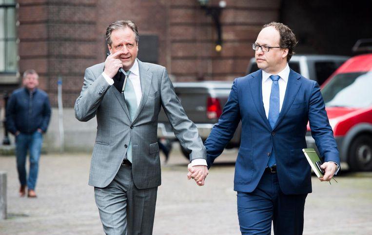 D66-onderhandelaars Alexander Pechtold en Wouter Koolmees arriveren uit solidariteit hand in hand op het Binnenhof. Beeld anp