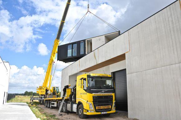 Een grote kraan hijst de containers op het dak.