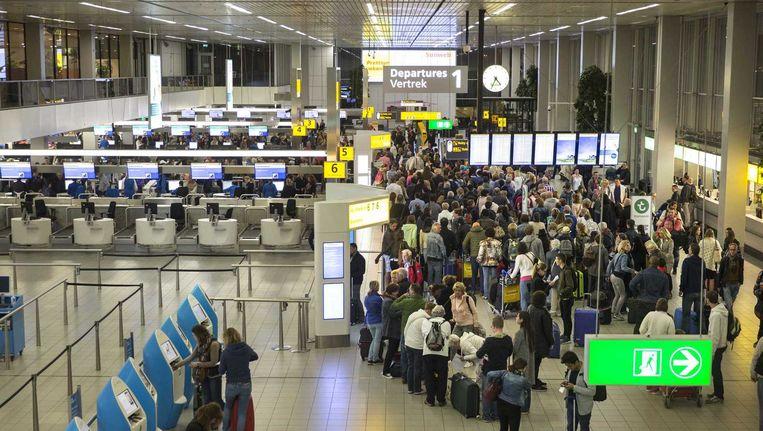 Drukte op Schiphol, afgelopen week. De vele controlepunten aan de gates zijn vervallen, daarvoor in de plaats zijn een aantal grote centrale controlepunten teruggekomen, waar passagiers door de beveiliging moeten. Beeld ANP