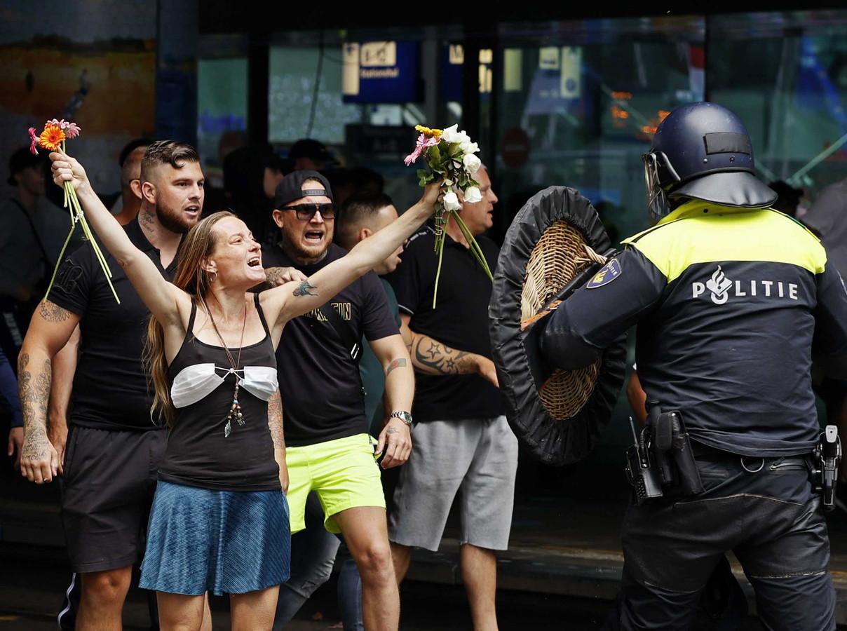 De beroemd geworden foto van het bloemenmeisje in de frontlinie van coronaprotest. De vrouw die op het Malieveld tussen hooligans en ME verzeild raakte, is de Nijmeegse Wendy Kroeze.
