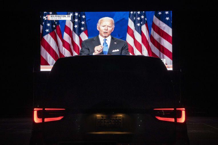 In Washington keken mensen op een drive-in party vanuit hun auto naar grote schermen waarop de speech van Biden te zien was.  Beeld AFP