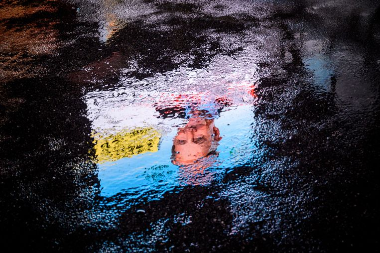 Een verkiezingsposter van de SVP met daarop Jean-François Thuillard reflecteert in een plas water in Chavannes de Bogis, Zwitserland. Beeld AFP