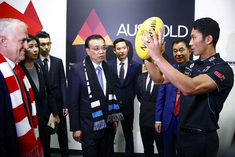 De Australische premier Malcolm Turnbull (rood-witte sjaal) en zijn Chinese collega Li Keqiang (zwart-witte sjaal) spreken met een Australian football-speler. Beeld AFP