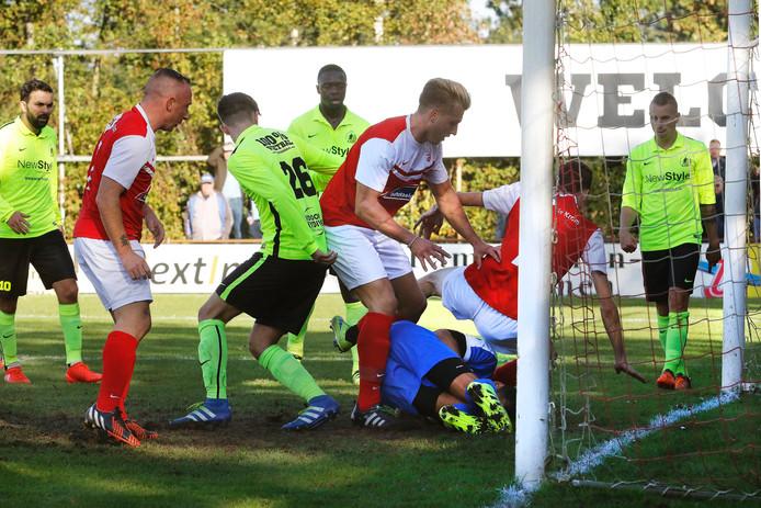 Hachelijke situatie voor het doel van Kruisland , maar de uitblinkende doelman van de Kruislanders Marc van Merrienboer heeft de bal klemvast, ondanks de RoodWit spelers Edwin Jaspers links van de doelman en Gianni Tiebosch , rechts van de doelman.