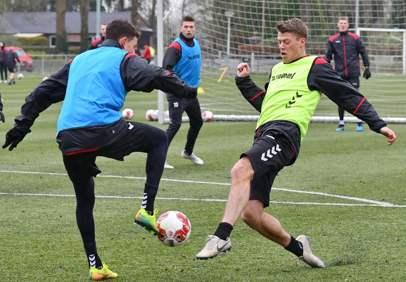 Joran Swart (rechts) en Jenthe Mertens betwisten elkaar de bal op de afsluitende training van Go Ahead Eagles richting de uitwedstrijd in Volendam. Voor Swart wordt dat zijn competitiedebuut in Deventer dienst.