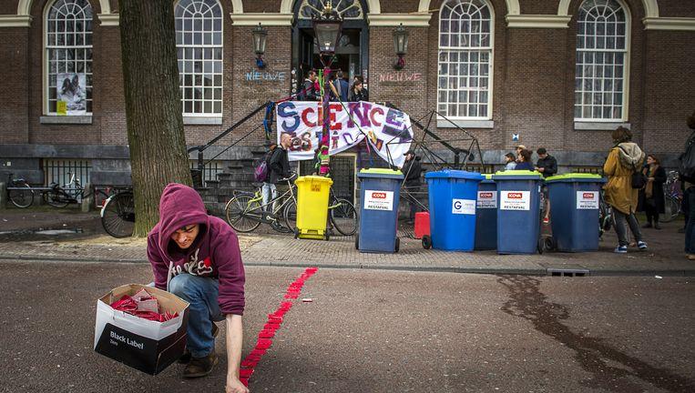 Een student trekt een rode streep bij het Maagdenhuis. Studenten maken een 'barricade van kunst' als reactie op de ontruiming. Beeld anp