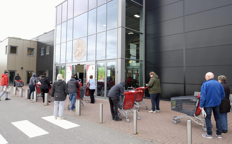 Mensen in de rij voor een supermarkt in België. Vanaf morgen mogen ze alleen gereguleerd boodschappen doen.
