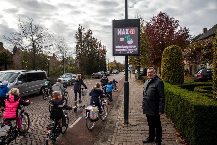 Wethouder Kees Marchal bij de snelheidsmeter en de schoolkinderen die er het eerst passeerden.