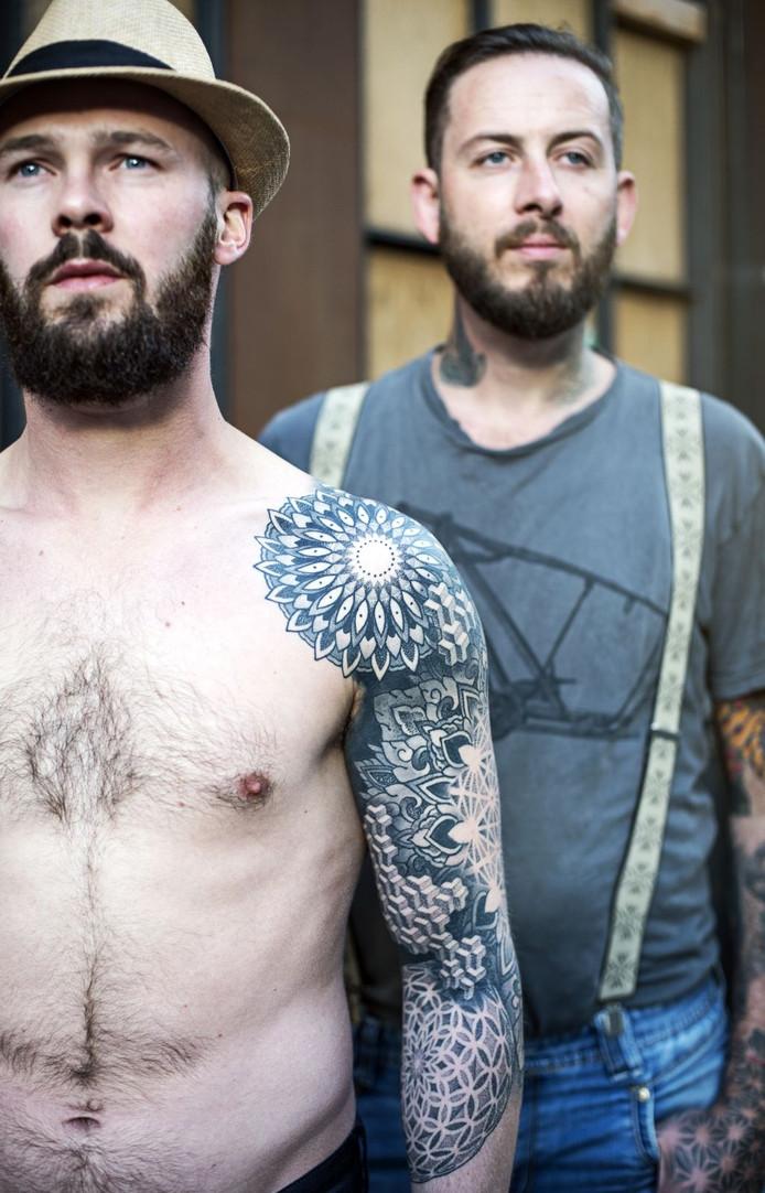 Tattoo artist Thomas (rechts) bij een van zijn tatoeages.