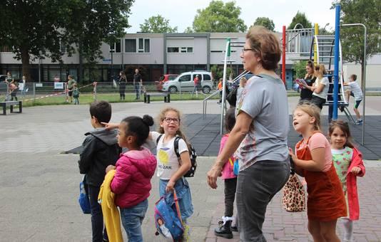 De laatste weken gaan de kleuters door coronaregels anders naar huis. Ouders wachten achter het schoolplein totdat hun kind naar hen toe komt.
