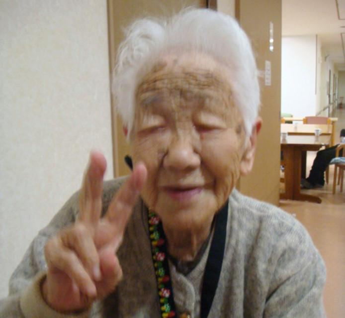 Japans oudste vrouw, de 115-jarige Kane Tanaka, maakt het vredesteken voor haar webcam