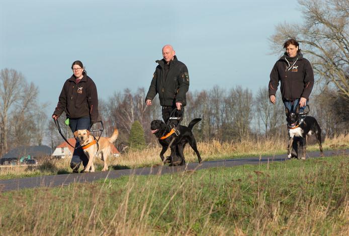 Vrijwilligers helpen Pieter-Jan Blok en Elly de Kuiper met de blindengeleidehonden.