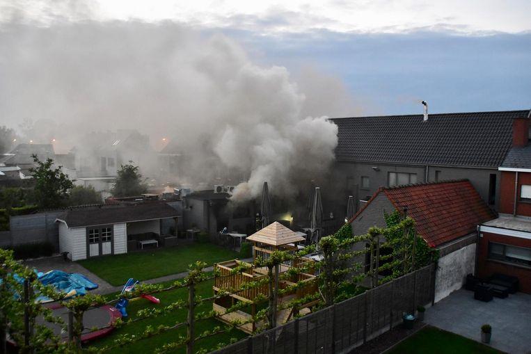 Een enorme rookwolk hangt aan de achterkant van het pand.