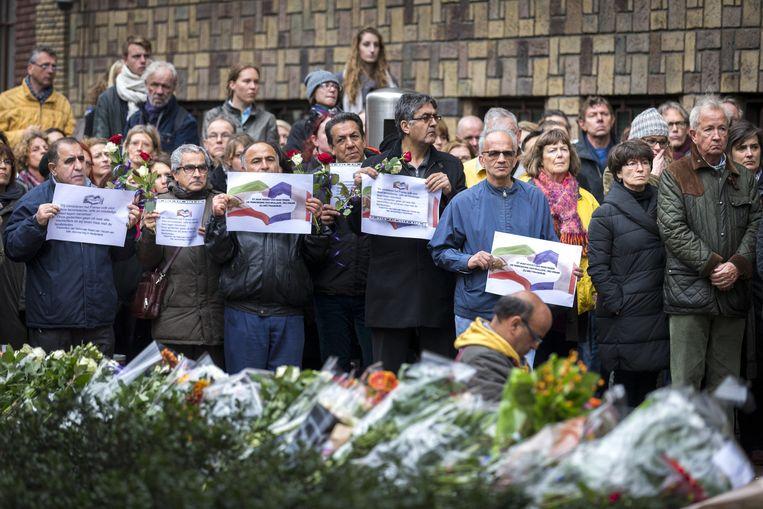 Mensen houden een minuut stilte bij de ambassade van Frankrijk in Den Haag. Beeld anp