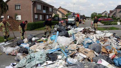 Vuilniswagen dumpt smeulend afval op straat