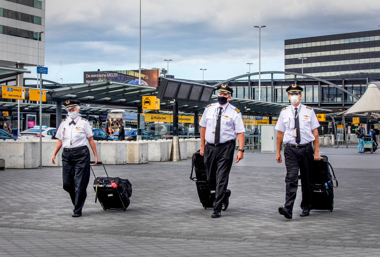Piloten lopen op Schiphol met mondkapjes op. Beeld Raymond Rutting / de Volkskrant