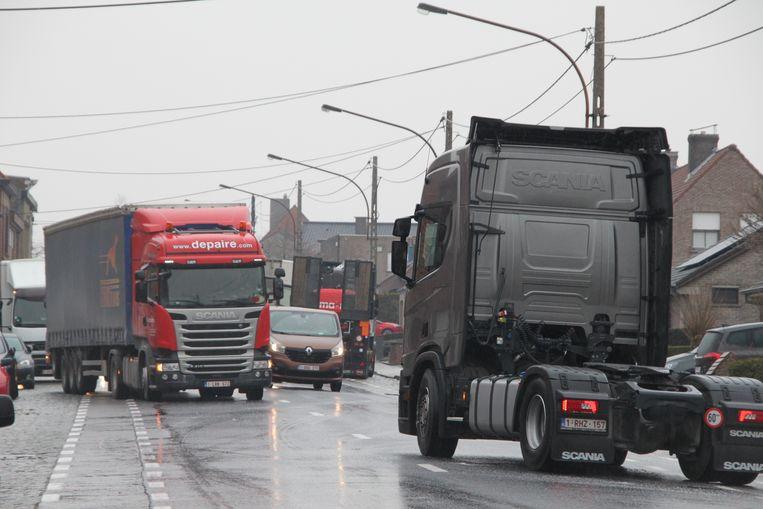 Vrachtwagens hebben alle moeite om een licht hellende straat in Moen (Zwevegem) op te rijden.