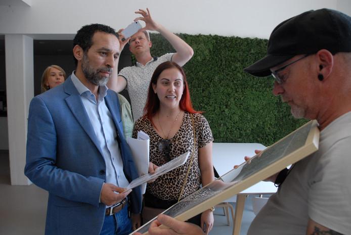 Zayaz-directeur Mohammed Acharki neemt de collage, waarop enkele foto's van huiselijke gebreken als gevolg van de renovatie bijeen zijn gebracht, in ontvangst van de bewoners Leo de Kok en Lana Kuenen.