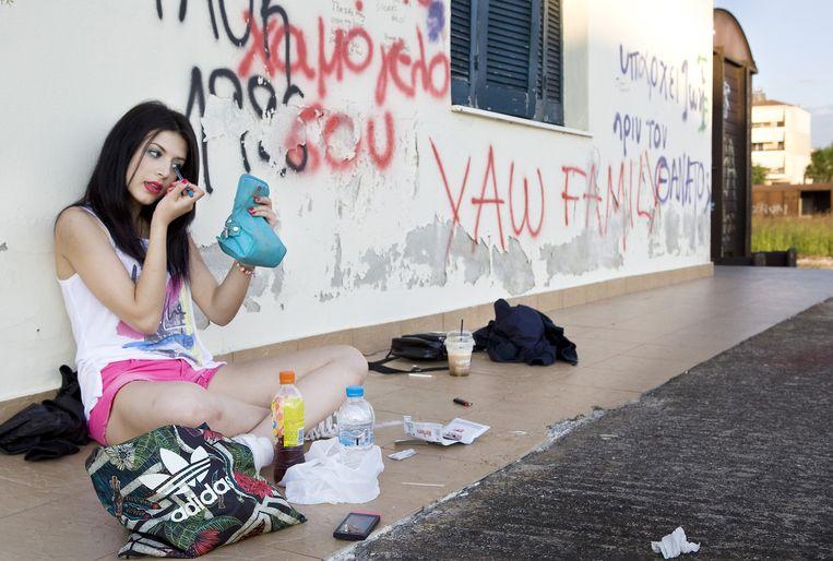 Meisje doet haar make-up in afwachting van de komst van haar vriend achter het station van Drama, Griekenland. Beeld Io Cooman