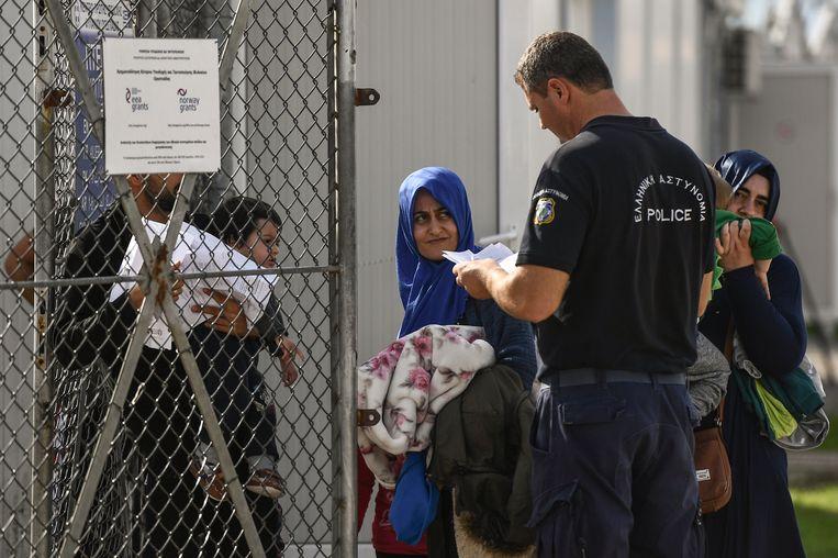 Vluchtelingen tonen hun papieren aan een politieagent bij een asielzoekerscentrum in het Griekse Fylakion Beeld AFP