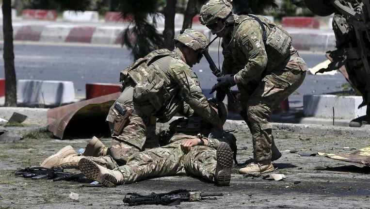 Amerikaanse soldaten snellen een gewonde kompaan te hulp na een bomaanslag in Kabul.