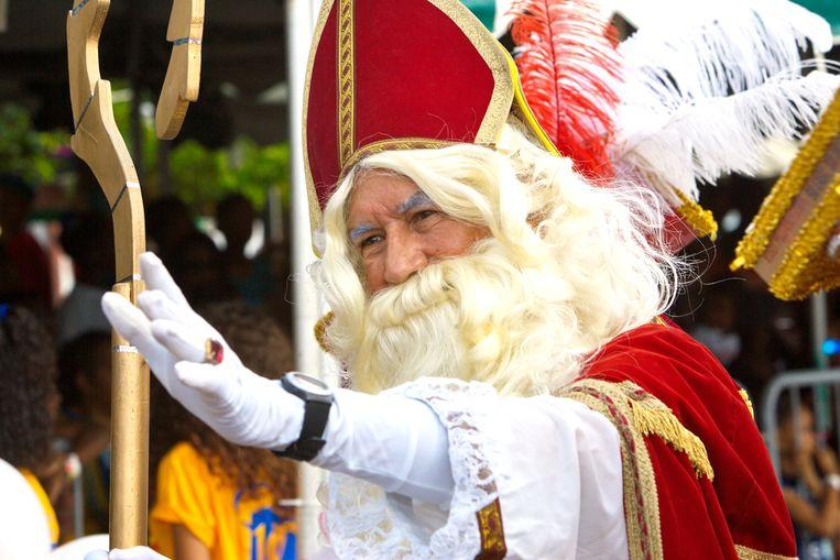 Sinterklaas zwaaiend te paard tijdens zijn intocht op Curaçao in 2016. De goedheiligman toen in Willemstad al Pieten in alle kleuren van de regenboog aan zijn zijde. Beeld Hollandse Hoogte /  ANP
