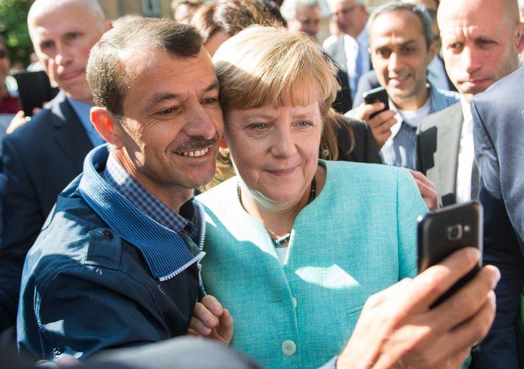 De Duitse bondskanselier Angela Merkel neemt een foto's met vluchtelingen in Berlijn. Beeld AP