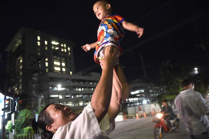 Een vrouw tilt haar kind op bij het ziekenhuis waar de Thaise voetballers opgenomen zijn.